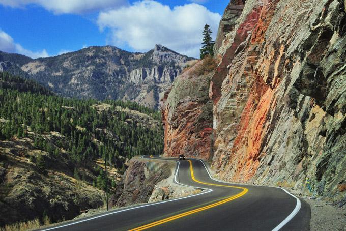 Million Dollar Highway, Colorado, car driving through mountains, trees.