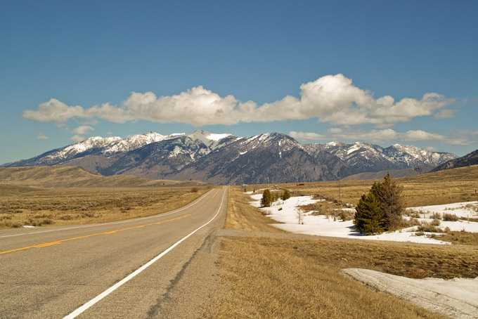 Montana road, snow-capped mountains, blue skies