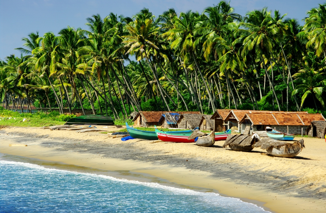 Beach huts and boats on the beach in Goa