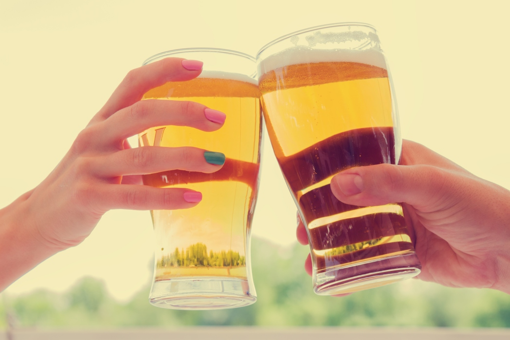 Two people clinking beer glasses