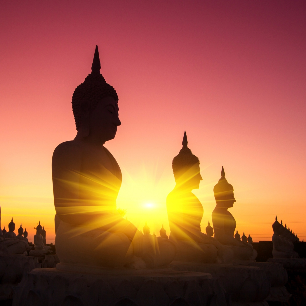 Statues of Buddha with the sun rising behind