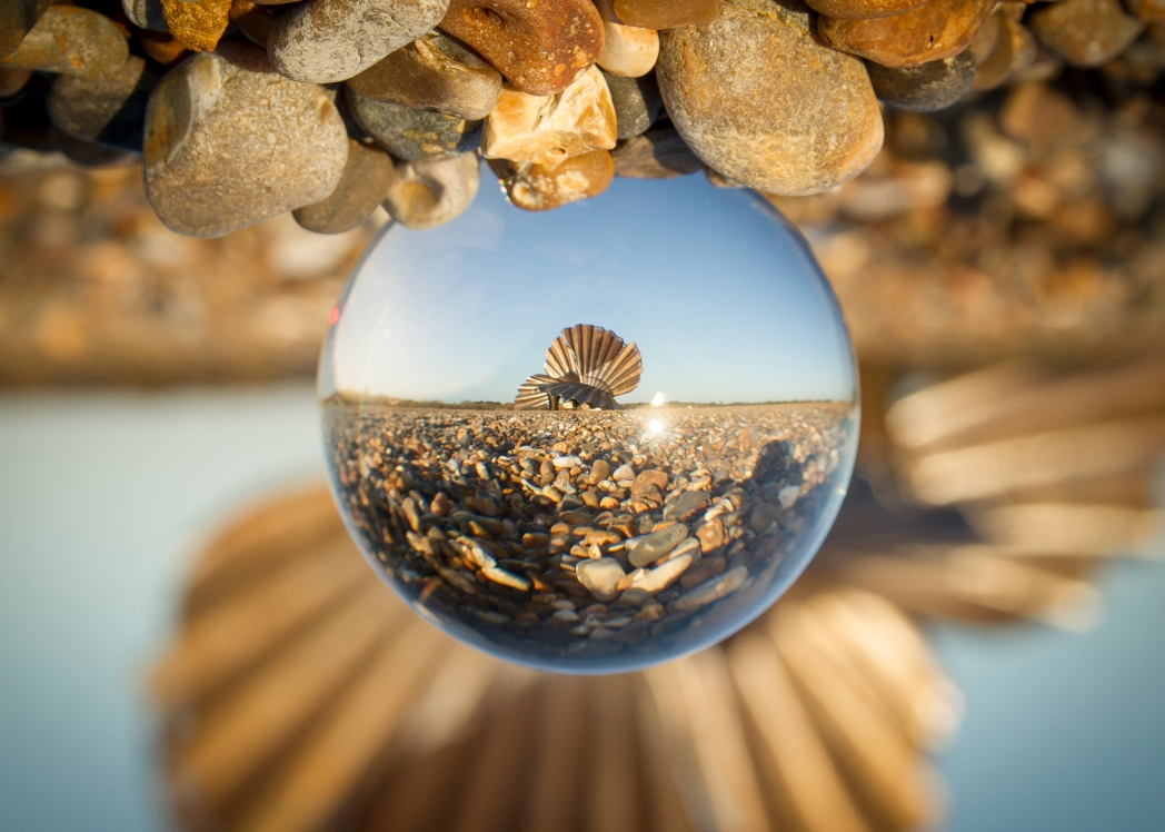 Aldeburgh, crystal ball on the pebble beach reflecting scallop statue