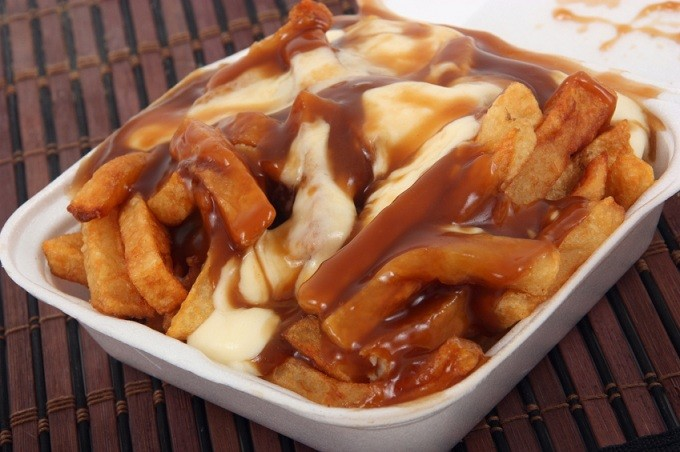 Chips with gravy and cheese in a white box, poutine, Canada.