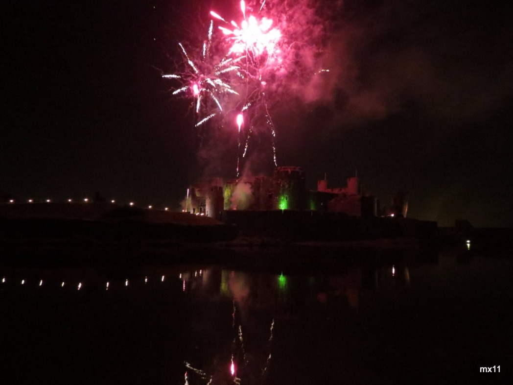 Pink fireworks exploding in the night sky above Cardiff Castle