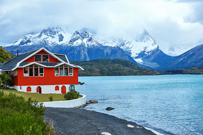Cabin by lake and snowy mountains, Chile.