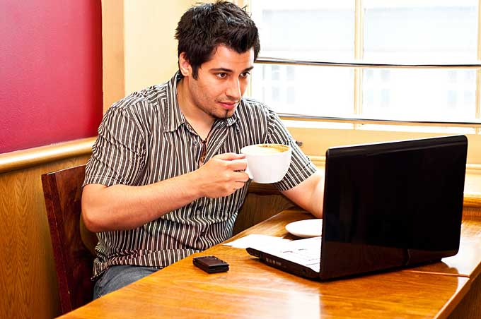 man on laptop in coffee shop