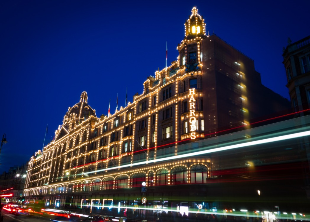 Harrods at night lit up with a red London bus speeding by in front of it