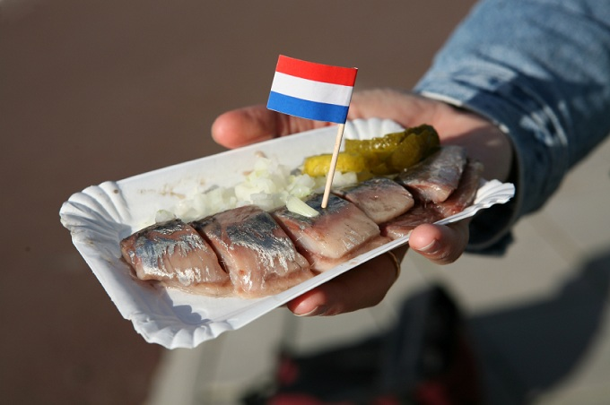 Pickled herring and onions in a tray with a Dutch flag on a cocktail stick in it.