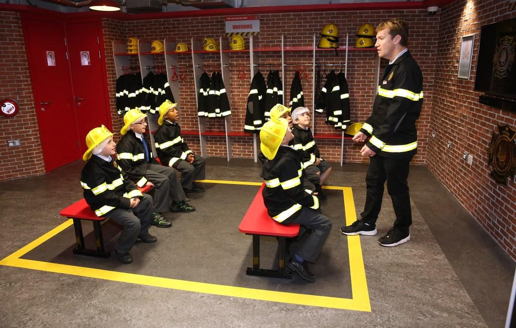 Kids receiving a briefing from a fireman at Kidzania