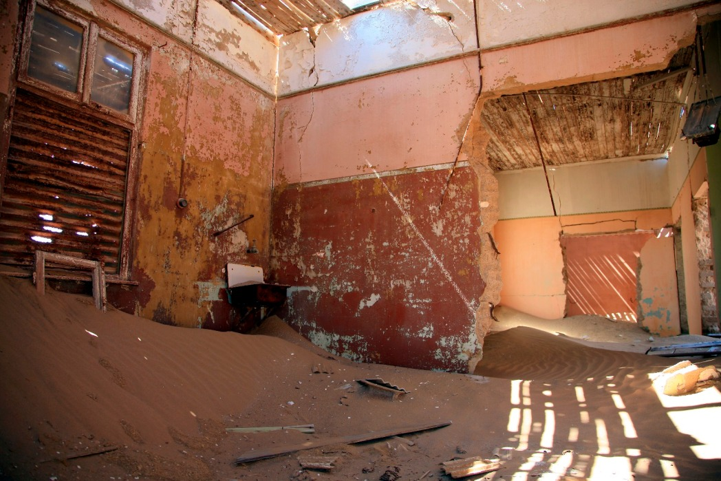 Interior of desalate house and sand dune in Kolmanskop, Namibia