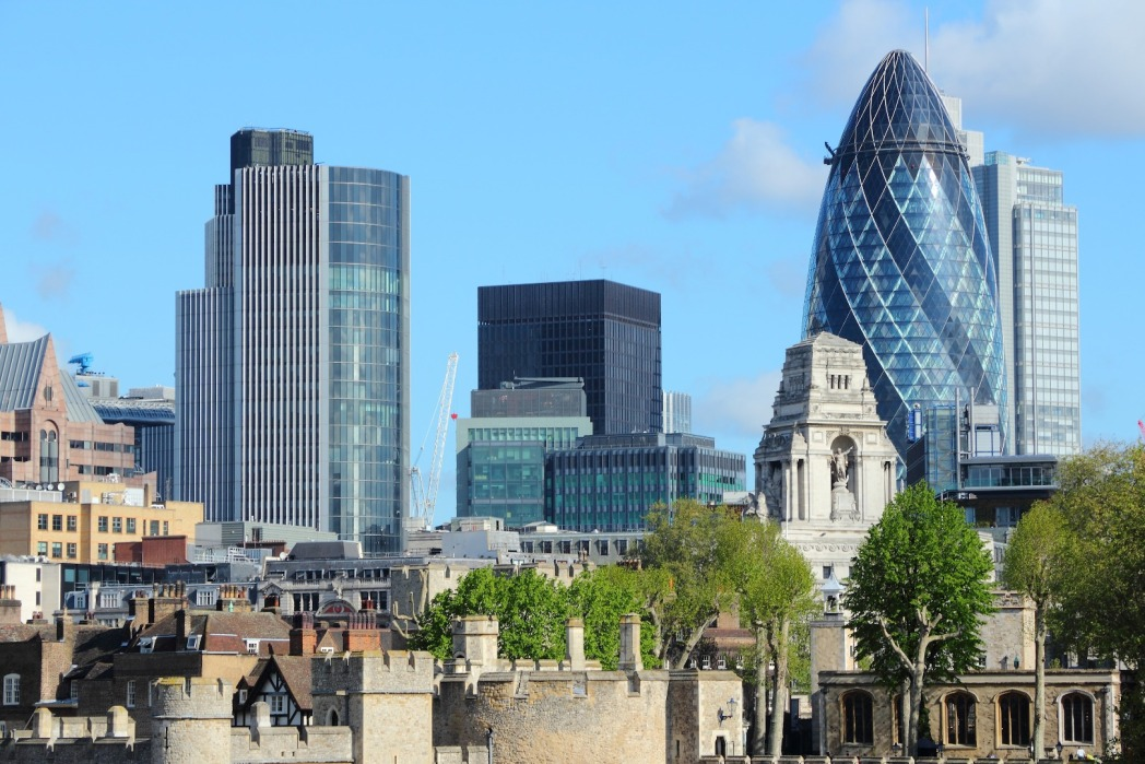 London skyline featuring the Gherkin, blue clear skies, green trees in foreground