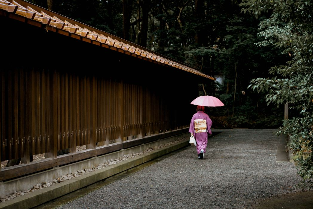 A woman walking into the woods at Meji Jingu shrine in Tokyo