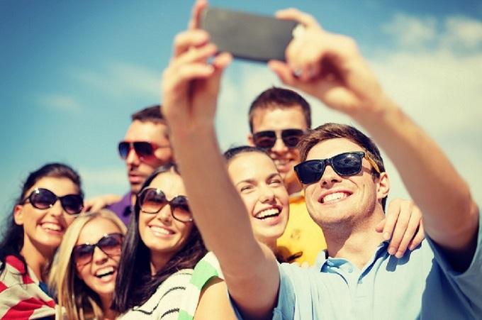 Group of friends taking a selfie on beach.