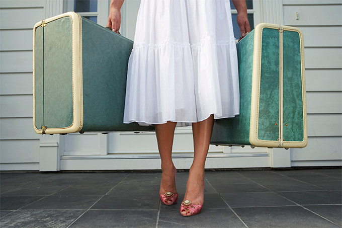 Woman in white dress holding 2 old fashioned blue suitcases.