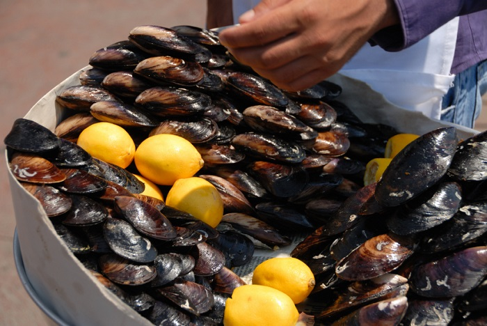 Bowl of stuffed mussels with lemon.